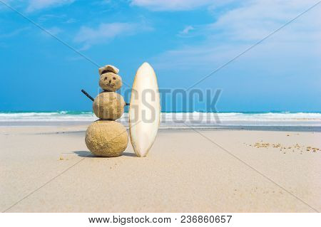 Sandman With Blue Sea Background. Handmade Yellow Sand Surfer Holding A White Surf Board On A Clean