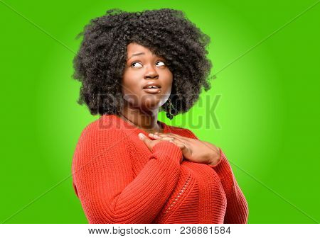 Beautiful african woman having charming smile holding hands on heart wanting to show love and sympathy