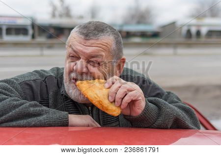 Hungry Senior Driver Eating Patty Near His Car