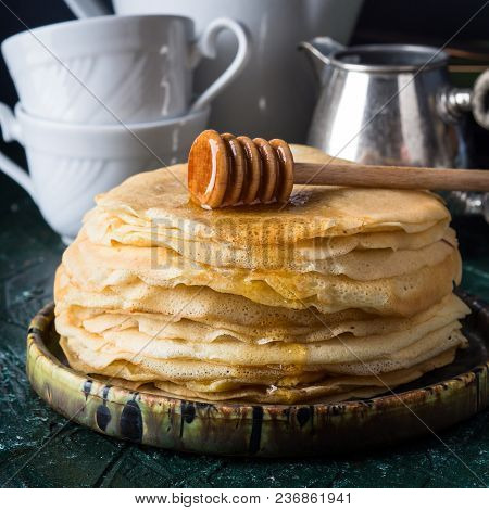 Stack Of Crepes With Poured Honey On Dark Background