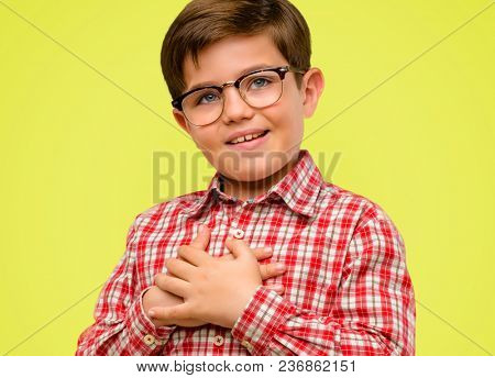Handsome toddler child with green eyes having charming smile holding hands on heart wanting to show love and sympathy over yellow background