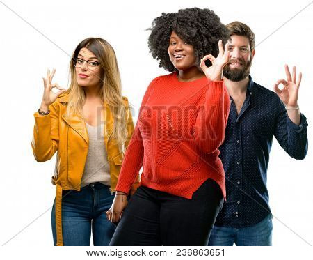 Group of three young men and women doing ok sign with hand, approve gesture