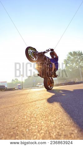 Ivano-frankivsk, Ukraine - 9 August 2015 : Photo Of Biker Is Doing Extreme Trick On One Cycle On Blu