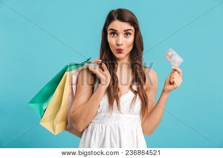 Portrait of a pretty girl in summer dress holding shopping bags and showing credit card isolated over blue background