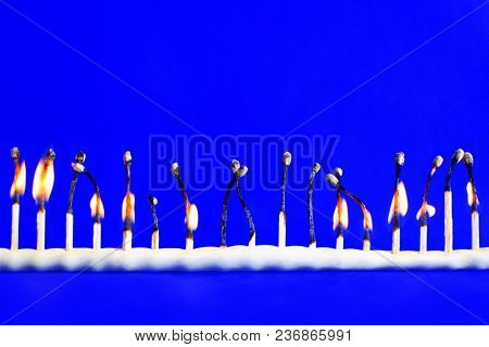 Line Of Seventeen Burned Safety Matches On Bright Blue Background With Copy Space For Text. Concept