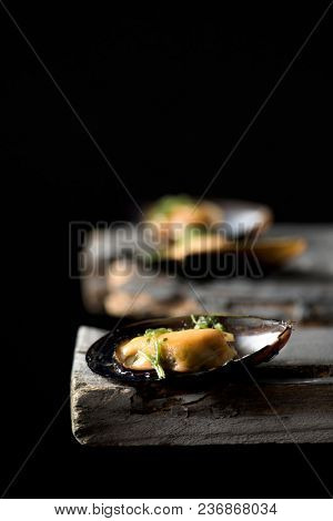 closeup of some moules mariniere, a french recipe of mussels, on a rustic wooden table against a black background, with some blank space on top