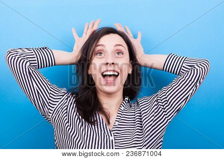 Young Woman Making Silly Faces On Blue Background In Studio