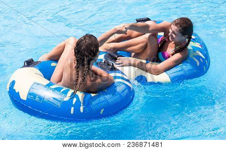 Two Young Girls Having Fun In The Swimming Pool
