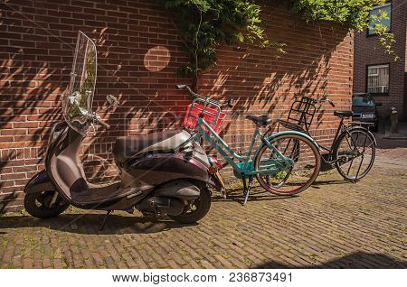 Bicycles And Scooter In Front Of The Bricked Wall And Door On Sunny Day At Weesp. Quiet And Pleasant