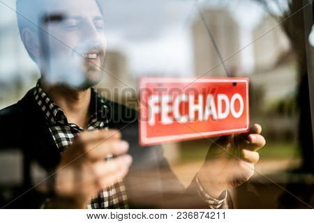 Business owner turning as closed (Fechado in portuguese) for business sign in their storefront window