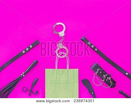 Different Sex Toys Are In The Background Of Fuchsia. Steel Handcuffs Are Fastened To The Handles Of