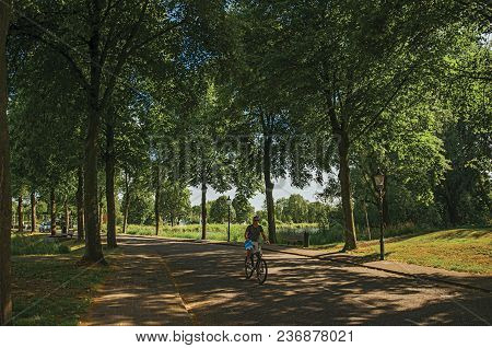 Weesp, Northern Netherlands - June 23, 2017. Man Riding Bicycle On A Street In The Shade Of Leafy Tr