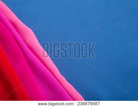 Blue Fabric Background With Beautiful And Pink Folds
