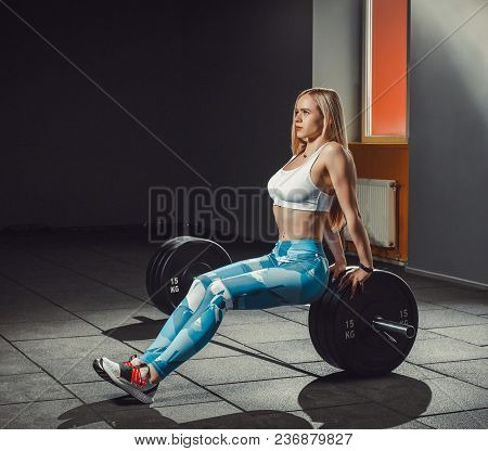 Sexy European Athletic Fitness Girl Working Out In Gym. Fitness Woman Sits On Barbell Or Lean On Bar