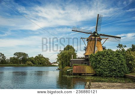 Wooden Windmill Next To Wide River, Leafy Bushes And Green Lawn Under Sunny Blue Sky At Weesp. Quiet