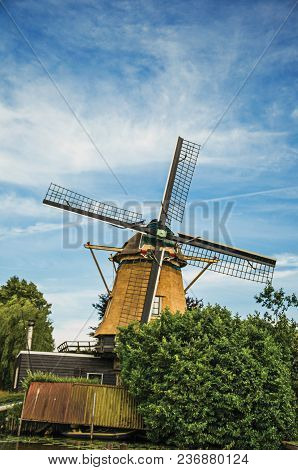 Wooden Windmill, Leafy Bushes And Sunny Blue Sky At Weesp. Quiet And Pleasant Village Full Of Canals