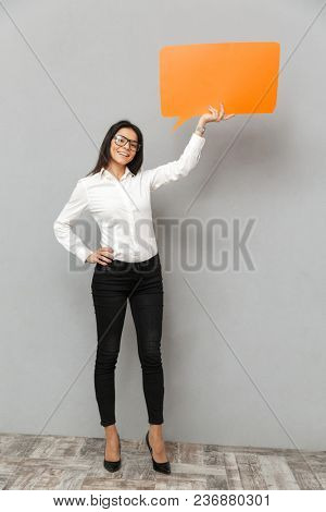 Full length image of business woman wearing formal outfit holding empty copyspace bubble for your text and smiling on camera, isolated over gray background