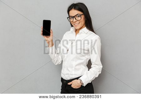 Photo of elegant young woman 30s in formal wear standing with smartphone in hands and demonstrating black screen on camera isolated over gray background