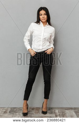 Full length image of attractive woman in white shirt and black trousers smiling at camera while posing with arms in pockets isolated over gray background