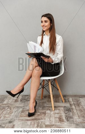 Full length image of business woman with long brown hair in formal wear sitting on chair and looking aside while holding folder with documents isolated over gray background