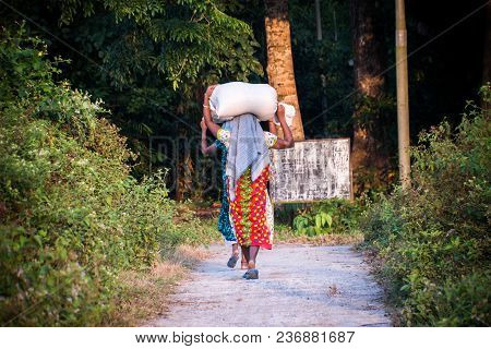 Indian Woman Carrying A Bundle On Her Head. Indian Girls Are Carrying Two Big Bags On Their Head On