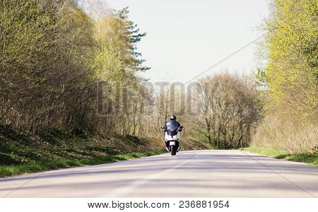 A Man  Riding A Motorcycle Scooter On Roads Out Of Town And Crowds