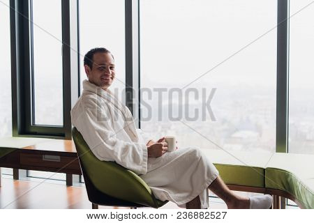 Young Handsome Carefree Man Near Modern Full Length Window Enjoying A Cup Of Coffee While Looking Ou