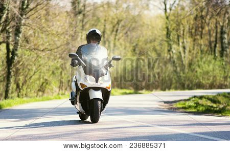 A Man On A Motorcycle Scooter Comes Out Of The Curve On The Road Through The Forest Landscape