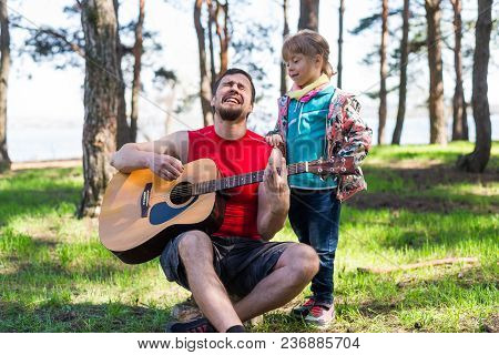 Family Duet: Dad Playing The Guitar With His Daughter, Free Space For Your Text.
