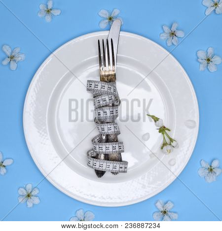 A Fork With A Knife Wrapped In A Measuring Tape Lie On A White Round Ceramic Plate, A Blue Backgroun