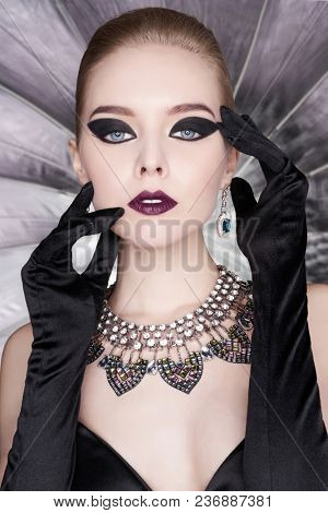 Fashion studio photo of beautiful elegant woman with bright makeup and with set jewelry. Fashion arrow shape. Woman in necklace with ring and earrings. Glamorous Gatsby style