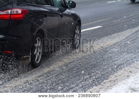 Closeup Rear View Of A Car Dark Color Wheel Tire Going Through Snow On A City Road Traffic With Moti