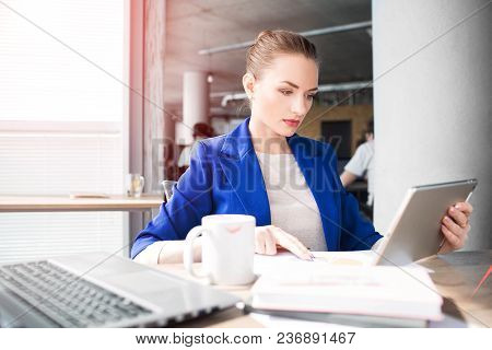 Busy Woman Is Working. She Is Looking To The Tablet's Screen And Working With Papers At The Same Tim