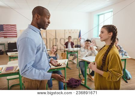 Side View Of African American Teacher Gesturing And Talking To Schoolgirl With Classmates Sitting Be