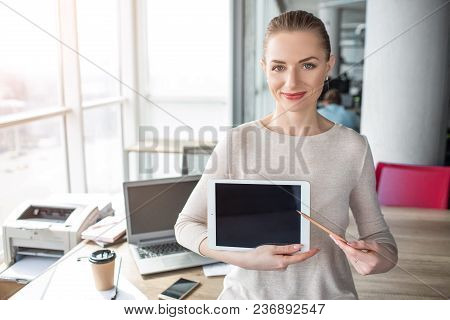 A Picture Of Happy And Cheerful Woman Having Laptop In Her Hands. She Has A Pen In Her Left Hand And