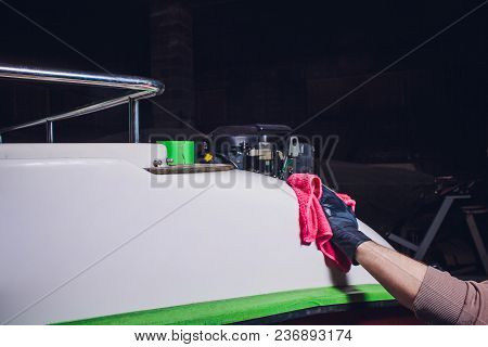 Yacht Maintenance. A Man Polishing Side Boat By Polishing Grinder Machine In The Marina