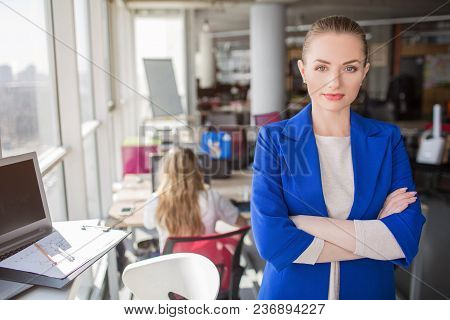 A Portrait Of Business Lady Standing Neat Window With Her Hands Crossed. She Is Looking Straight To
