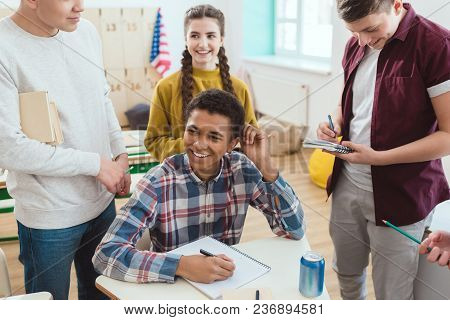 Happy African American Schoolboy Writing In Notebook While His Classmates Standing Around