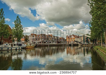 Brick Houses, Moored Boats And Bascule Bridge Reflected In Wide Canal Water Surface On Sunset In Wee