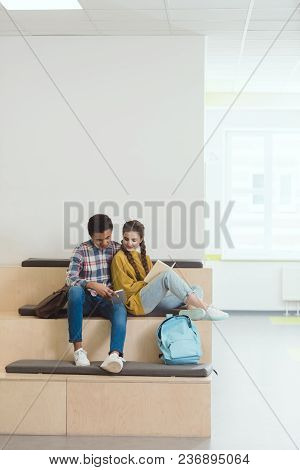 High School Students Couple Doing Homework At School Corridor Together