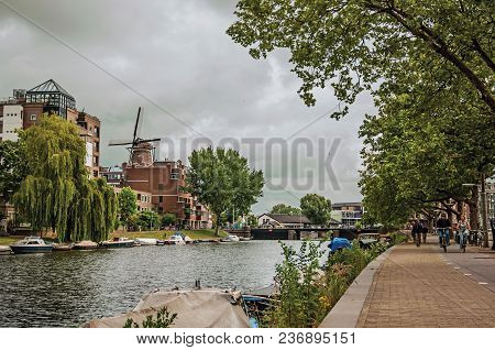 Amsterdam, Northern Netherlands - June 25, 2017. Wooded Canal With Buildings, Moored Boats, Cyclists