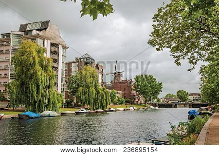 Big Wooded Canal With Modern Brick Buildings, Moored Boats And Cloudy Sky In Amsterdam. Famous For I