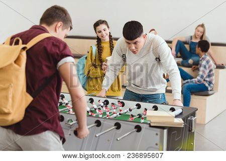 High School Students Playing Table Football At School Corridor