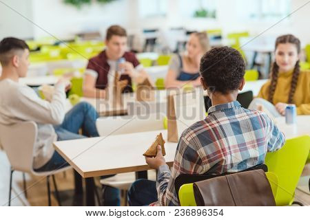 Group Of Teen Students Chatting While Taking Lunch At School Cafeteria