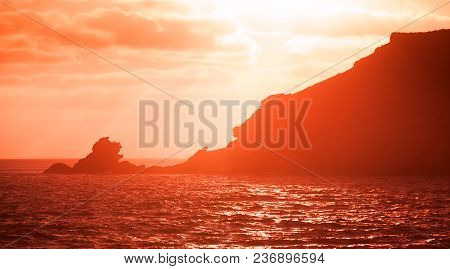 Portugal. Porto Santo Island. Landscape With Coastal Rocks In Red Evening Sunlight. Red Tonal Filter
