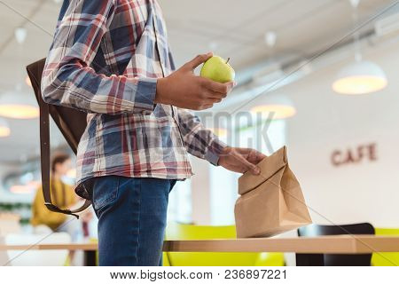 Cropped Shot Of African American Schoolboy With Apple And Lunch Bag At School Cafeteria