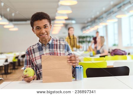 African American Schoolboy With Apple And Lunch Bag At School Cafeteria