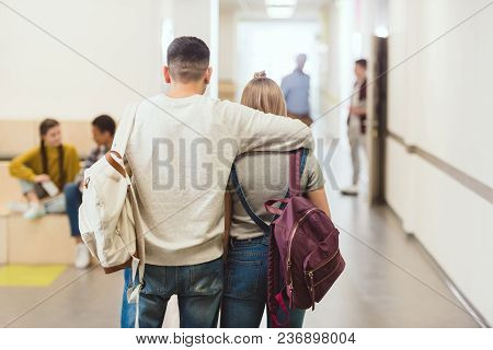 Back View Of Teenage Students Couple Walking By School Corridor And Embracing