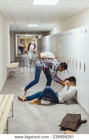 Schoolboy Being Bullied In School Corridor Under Lockers While Other Boy Running To Help Him