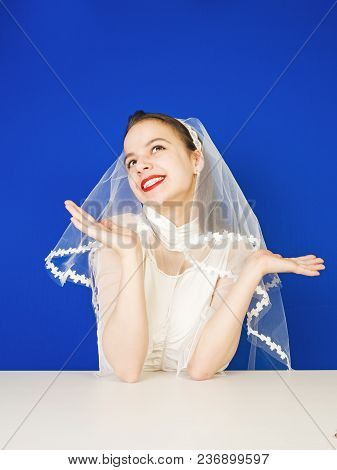 Beautiful Bride In A Wedding Dress Holding Hands Like A Scales, Looking At The Top A Girl In Doubt M